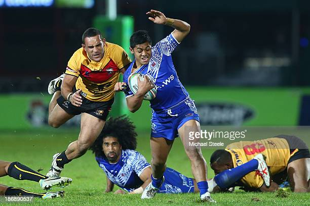 Anthony Milford of Samoa is held up by Paul Aiton of Papua New Guinea during the Rugby League World Cup Group B match between Papua New Guinea and...