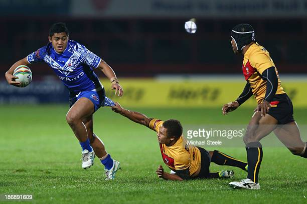 Anthony Milford of Samoa is held up by Ray Thompson of Papua New Guinea during the Rugby League World Cup Group B match between Papua New Guinea and...