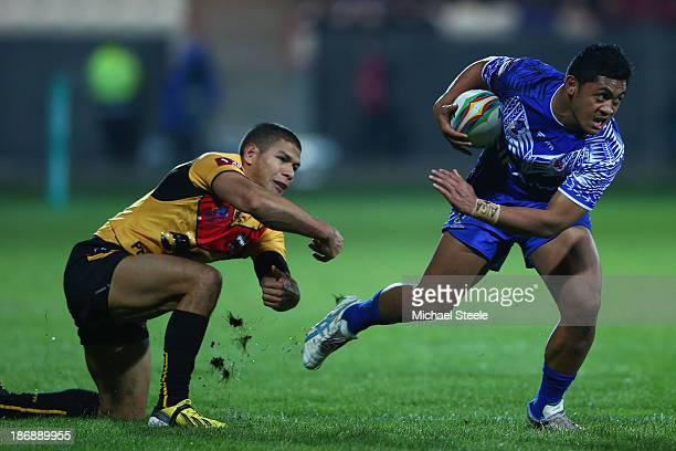 Anthony Milford of Samoa skips the challenge of David Mead of Papua New Guinea during the Rugby League World Cup Group B match between Papua New...