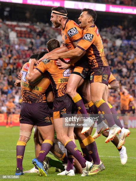 Anthony Milford of the Broncos is congratulated by team mates after scoring a try during the round 16 NRL match between the Brisbane Broncos and the...