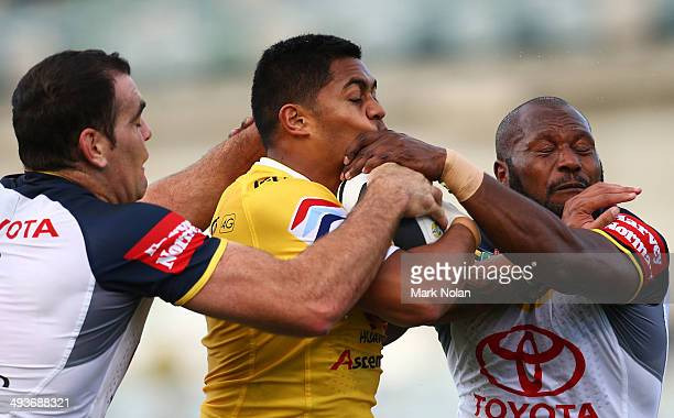 Anthony Milford of the Raiders is tackled by Kane Linnett and Robert Lui of the Cowboys during the round 11 NRL match between the Canberra Raiders...