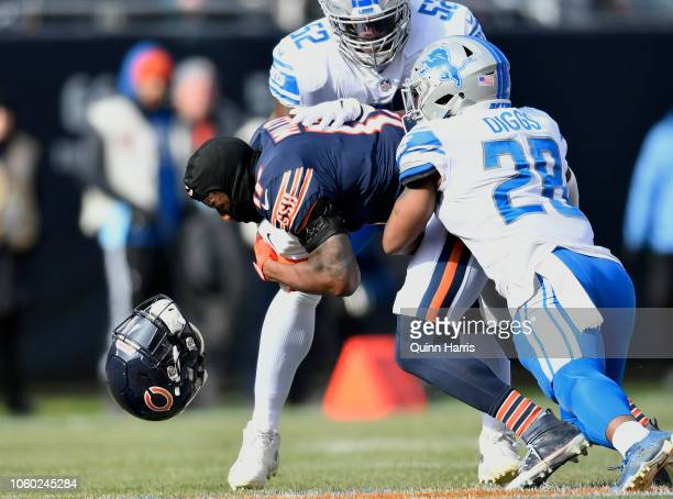 Anthony Miller of the Chicago Bears loses his helmet while being tackled by Quandre Diggs and Christian Jones of the Detroit Lions in the first...