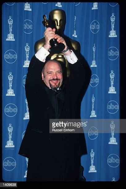 Anthony Minghella holds his award for Best Director for 'The English Patient' at the 69th Annual Academy Awards ceremony March 24 1997 in Los Angeles...