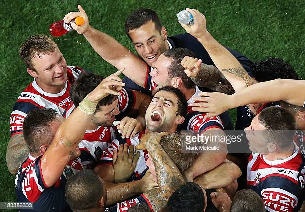 Anthony Minichiello of the Roosters celebrates with team mates at fulltime after winning the 2013 NRL Grand Final match between the Sydney Roosters...