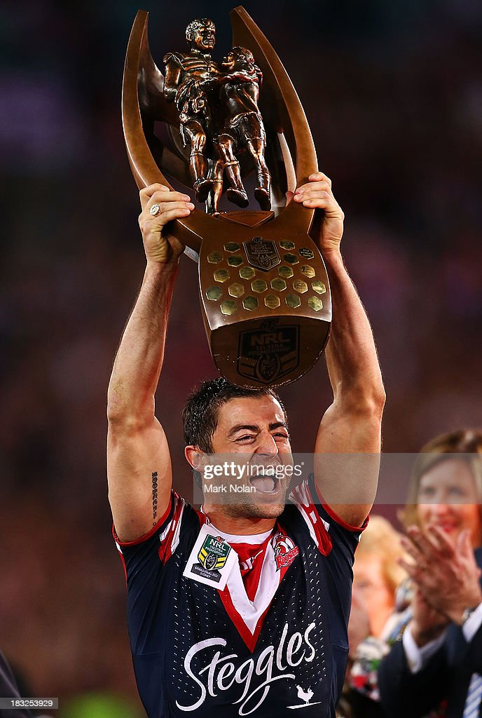 Anthony Minichiello of the Roosters holds up the NRL trophy after winning the 2013 NRL Grand Final match between the Sydney Roosters and the Manly Warringah Sea Eagles at ANZ Stadium on October 6, 2013 in Sydney, Australia.