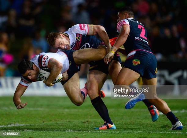 Anthony Minichiello of the Roosters is tackled by Brent Tate and Matthew Wright of the Cowboys during the round 10 NRL match between the North...