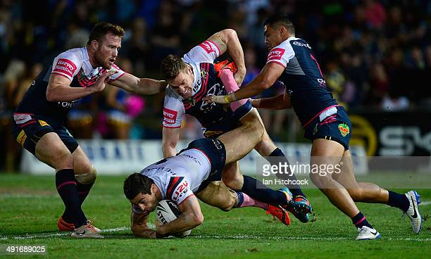 Anthony Minichiello of the Roosters is tackled by Brent Tate, Gavin Cooper and Matthew Wright of the Cowboys during the round 10 NRL match between...