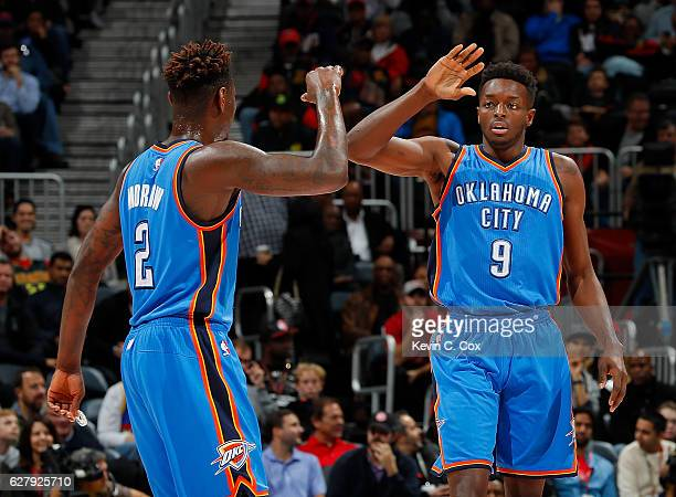 Anthony Morrow and Jerami Grant of the Oklahoma City Thunder react after a basket against the Atlanta Hawks at Philips Arena on December 5 2016 in...