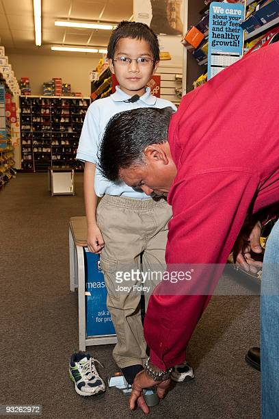 Anthony Munoz helps a young boy measure his foot with a Brannock device at Payless ShoeSource on November 20 2009 in Cincinnati Ohio