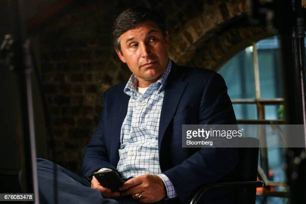 Anthony Noto chief financial officer and chief operating officer of Twitter Inc checks his smartphone before the start of a Bloomberg Television...