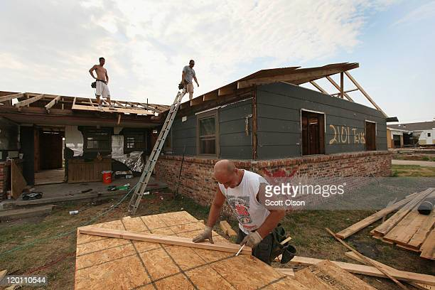 Anthony Owens repairs the roof of a tornado damaged home with James Davis and Dwain Payne July 30, 2011 in Joplin, Missouri. All three men came up...