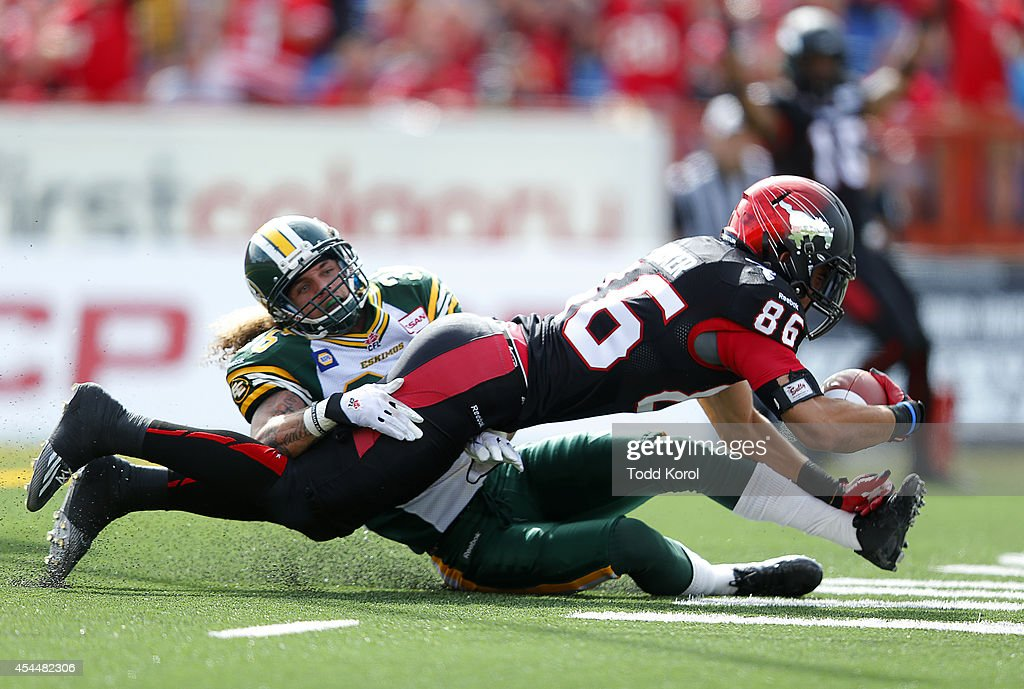 Anthony Parker #86 of the Calgary Stampeders dives in for a touchdown while Aaron Grymes #36 of the Edmonton Eskimos tries to stop him during the first half of their CFL football game September 1, 2014 at McMahon Stadium in Calgary, Alberta, Canada.