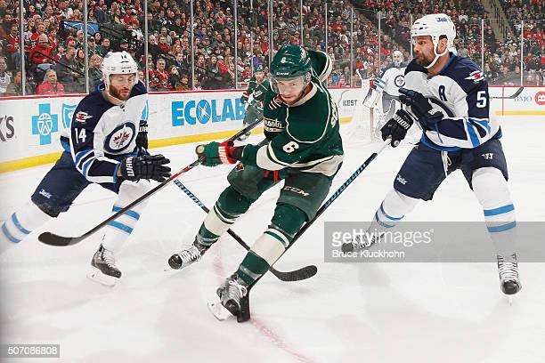 Anthony Peluso and Mark Stuart of the Winnipeg Jets defend Marco Scandella of the Minnesota Wild during the game on January 15 2016 at the Xcel...