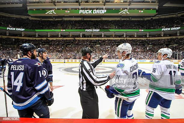 Anthony Peluso Mark Scheifele of the Winnipeg Jets Adam Cracknell and Jake Virtanen of the Vancouver Canucks are separated by linesman Lonnie Cameron...
