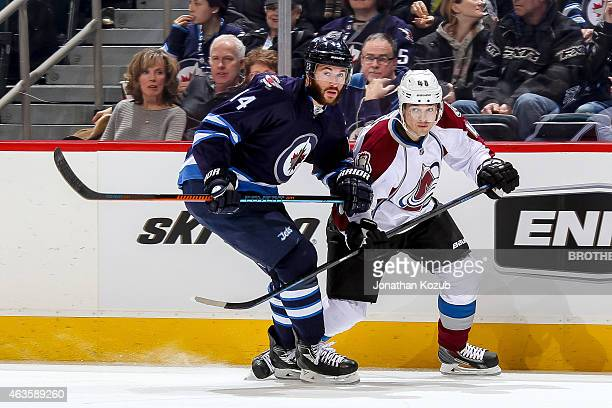 Anthony Peluso of the Winnipeg Jets and Daniel Briere of the Colorado Avalanche keep an eye on the play during third period action on February 8 2015...