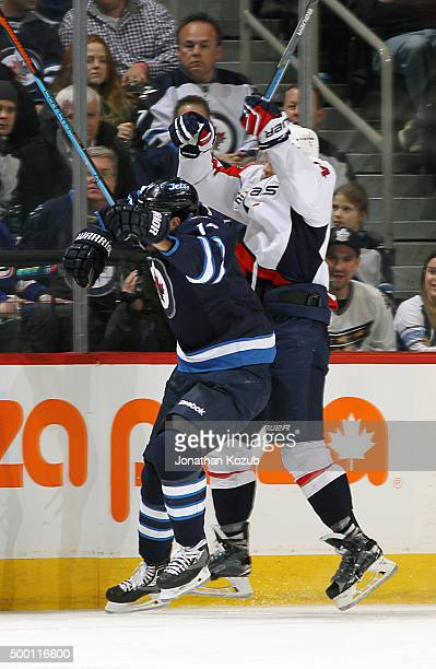Anthony Peluso of the Winnipeg Jets and John Carlson of the Washington Capitals collide along the boards during third period action at the MTS Centre...