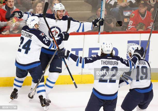 Anthony Peluso of the Winnipeg Jets celebrates with teammates Grant Clitsome Chris Thorburn and Jim Slater during a game against the Chicago...