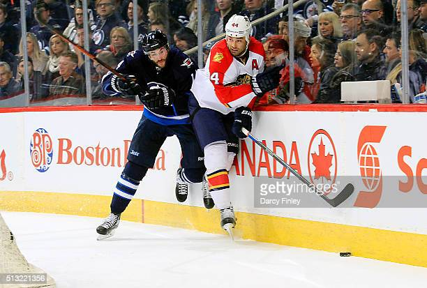 Anthony Peluso of the Winnipeg Jets checks Erik Gudbranson of the Florida Panthers into the boards during first period action at the MTS Centre on...