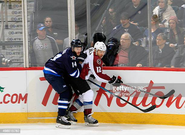 Anthony Peluso of the Winnipeg Jets checks Jarome Iginla of the Colorado Avalanche into the boards during second period action at the MTS Centre on...