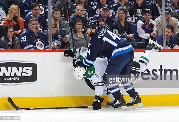 Anthony Peluso of the Winnipeg Jets checks Jason Demers of the Dallas Stars into the boards during third period action on January 31 2015 at the MTS...