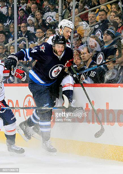 Anthony Peluso of the Winnipeg Jets checks Taylor Chorney of the Washington Capitals into the boards during first period action at the MTS Centre on...