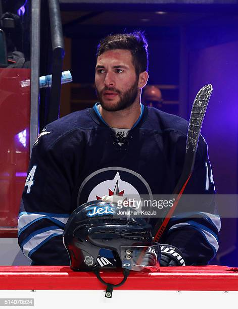 Anthony Peluso of the Winnipeg Jets looks on from the bench prior to puck drop against the Florida Panthers at the MTS Centre on March 1 2016 in...