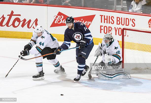 Anthony Peluso of the Winnipeg Jets MarcEdouard Vlasic and goaltender Alex Stalock of the San Jose Sharks eye the loose puck during second period...