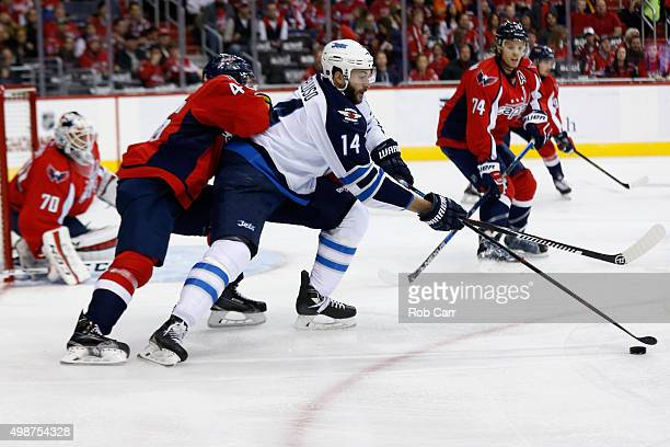 Anthony Peluso of the Winnipeg Jets moves the puck in front of Michael Latta of the Washington Capitals in the first period at Verizon Center on...