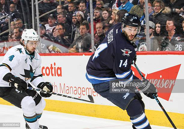 Anthony Peluso of the Winnipeg Jets plays the puck along the boards as Brenden Dillon of the San Jose Sharks defends during third period action at...