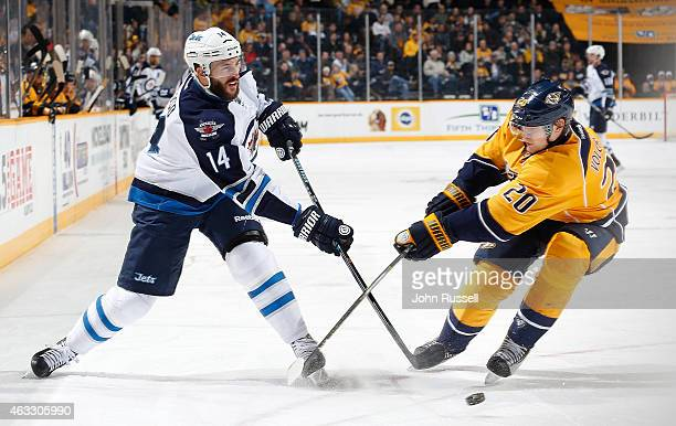 Anthony Peluso of the Winnipeg Jets shoots the puck against Anton Volchenkov of the Nashville Predators during an NHL game at Bridgestone Arena on...