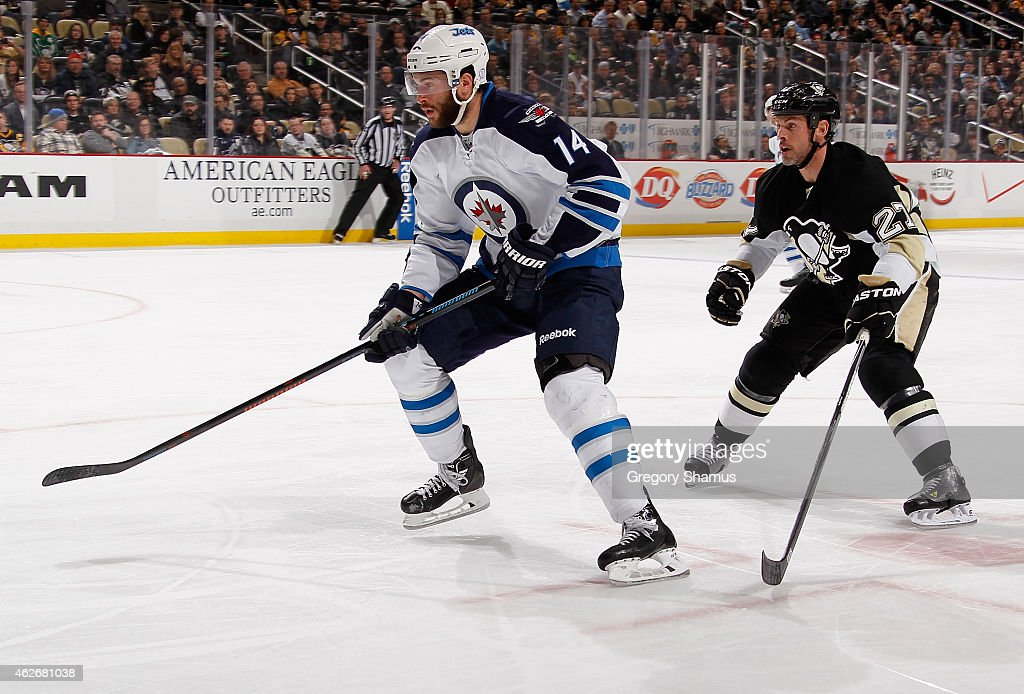 Anthony Peluso #14 of the Winnipeg Jets skates in front of Craig Adams #27 of the Pittsburgh Penguins at Consol Energy Center on January 27, 2015 in Pittsburgh, Pennsylvania.