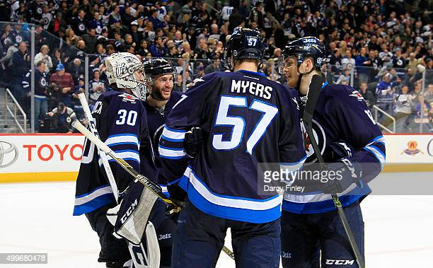Anthony Peluso Tyler Myers and Adam Lowry of the Winnipeg Jets congratulate goaltender Connor Hellebuyck after a 61 victory over the Toronto Maple...