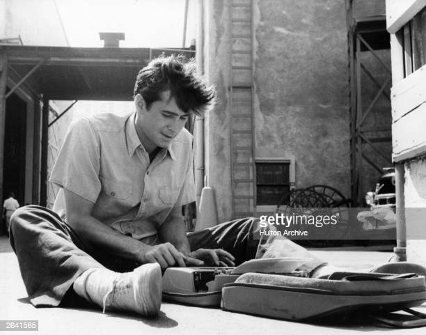 Anthony Perkins the American film actor most renowned for his part in Hitchcock's 'Psycho' is pictured during a leisure period on a film set typing a...