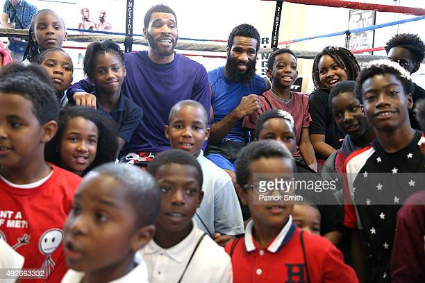 Anthony Peterson and Lamont Peterson pose with children from the Boys and Girls Club during fighter media workouts in the Alexandria Boxing Club at...