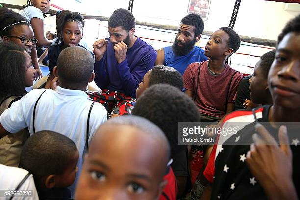 Anthony Peterson and Lamont Peterson talk with children from the Boys and Girls Club during fighter media workouts in the Alexandria Boxing Club at...