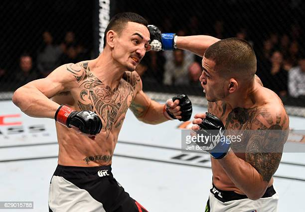Anthony Pettis punches Max Holloway in their interim UFC featherweight championship bout during the UFC 206 event inside the Air Canada Centre on...