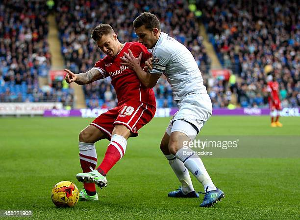 Anthony Pilkington of Cardiff holds off the challenge of Jason Pearce of Leeds United during the Sky Bet Championship match between Cardiff City and...