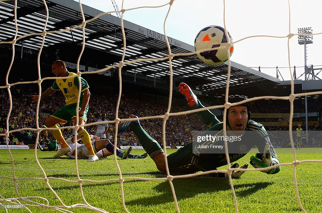 Anthony Pilkington of Norwich City turns to celebrate his goal as Petr Cech of Chelsea watches the ball go into the net during the Barclays Premier League match between Norwich City and Chelsea at Carrow Road on October 6, 2013 in Norwich, England.