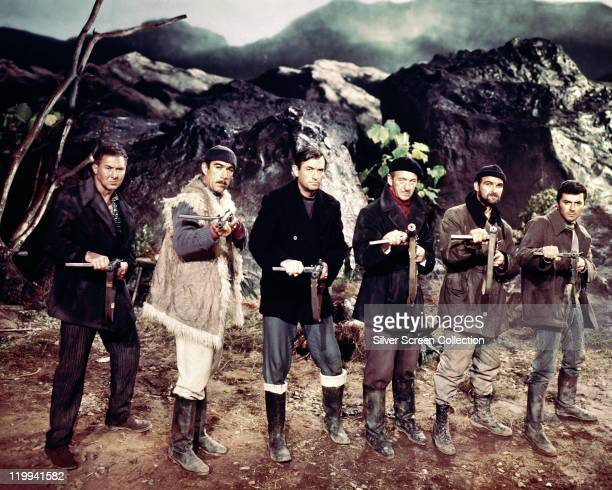 Anthony Quayle Anthony Quinn Gregory Peck David Niven Stanley Baker and James Darren stand pointing the guns at the camera in a publicity still...
