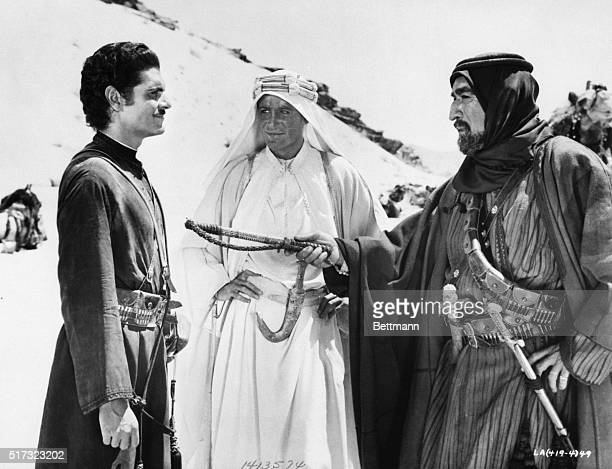 Anthony Quinn acting as Auda abu Tayi hands a sword to Omar Sharif who portrayed Sherif Ali ibn el Kharish Peter O'Toole stands in between O'Toole...
