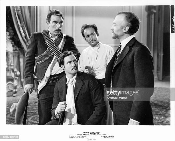 Anthony Quinn and Marlon Brando looking at businessman in a scene from the film 'Viva Zapata' 1952
