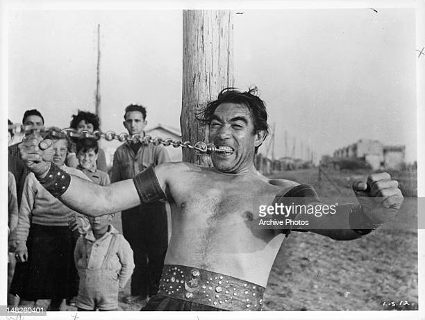 Anthony Quinn continues to bite down on a metal chain as he pulls it away from him in a scene from the film 'La Strada' 1954