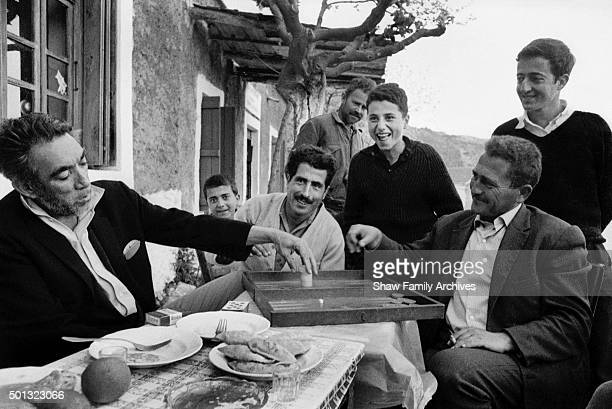 Anthony Quinn plays backgammon with locals in 1964 during the filming of 'Zorba the Greek' in Crete Greece
