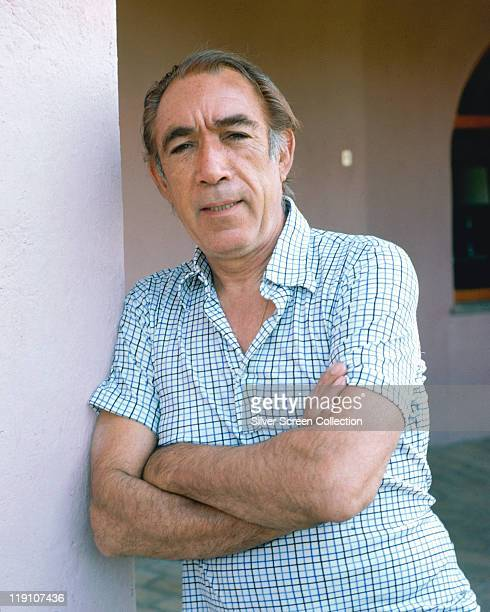 Anthony Quinn poses with his arms folded across his chest wearing a blueandwhite shortsleeved shirt circa 1975
