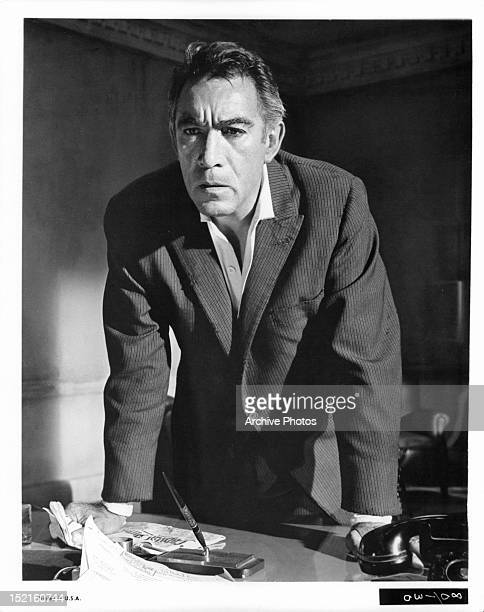 Anthony Quinn puts his hands on a desk in a scene from the film 'The Visit' 1964