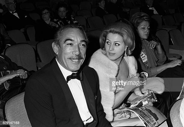 Anthony Quinn with his wife Jolanda Addolori seated in a theater for a formal event circa 1970 New York