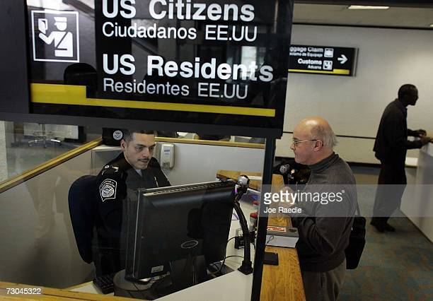 Anthony Ramos a Customs and Border Protection officer checks Martin Keenan in at the passport control area January 19 2007 at Miami International...