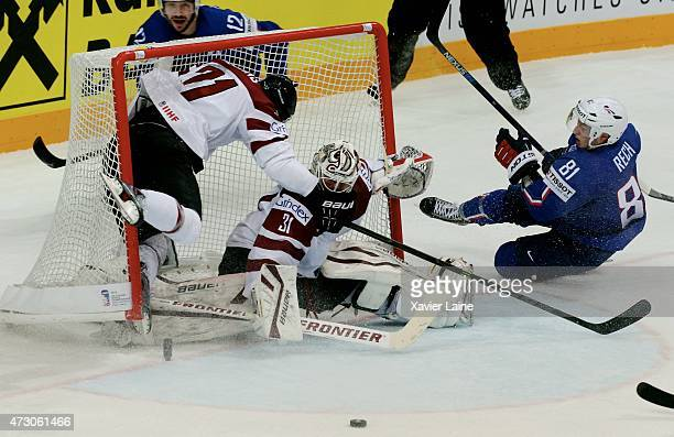 Anthony Rech of France is push by Robert Bukarts and Edgars Masalskis of Latviaduring the 2015 IIHF World Championship between Latvia and France at...