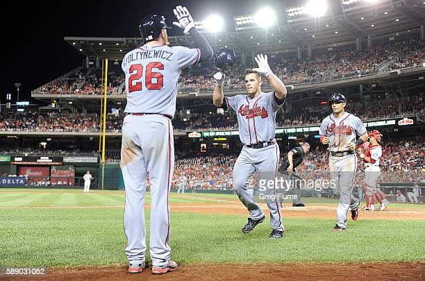 Anthony Recker of the Atlanta Braves celebrates with Mike Foltynewicz after hitting a home run in the sixth inning against the Washington Nationals...