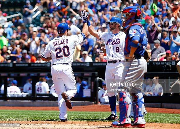 Anthony Recker of the New York Mets celebrates his first inning threerun home run against the Texas Rangers with teammate Kirk Nieuwenhuis at Citi...